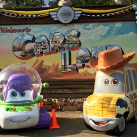 Pixar Fest Cars Land Billboard Concept – I came up with the idea of getting the Woody and Buzz cars (from the ending credits of Pixar's Cars) in front of the Cars Land Billboard and created the early designs of the hanging banner above.